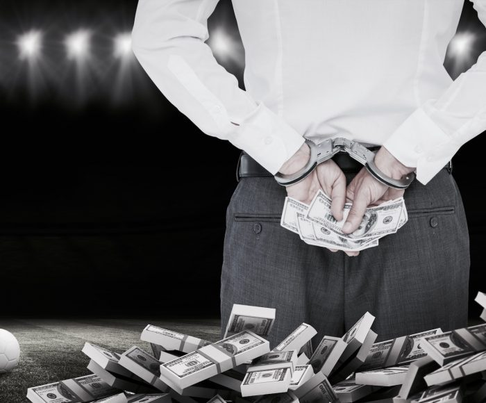 Composite image of businessman in handcuffs holding bribe
